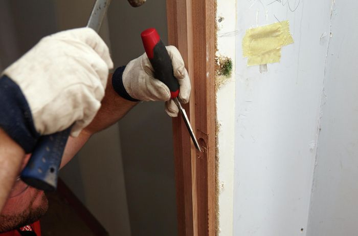 A hammer and chisel being used to enlarge the cavity cut out of the door frame