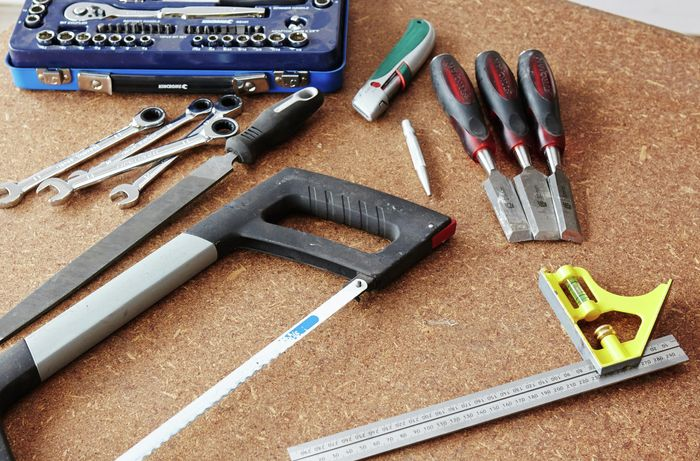 A square rule, saw, chisels, spanners and boxcutter