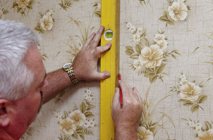 A spirit level being used to rule a straight line on a wallpapered wall