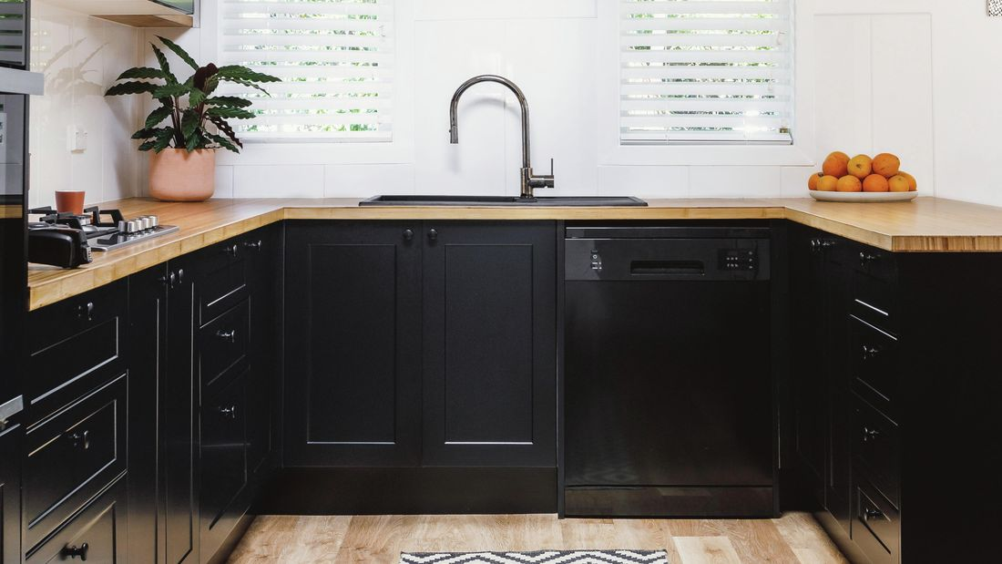 kitchen with black cabinets and appliances, white walls and plantain shutters
