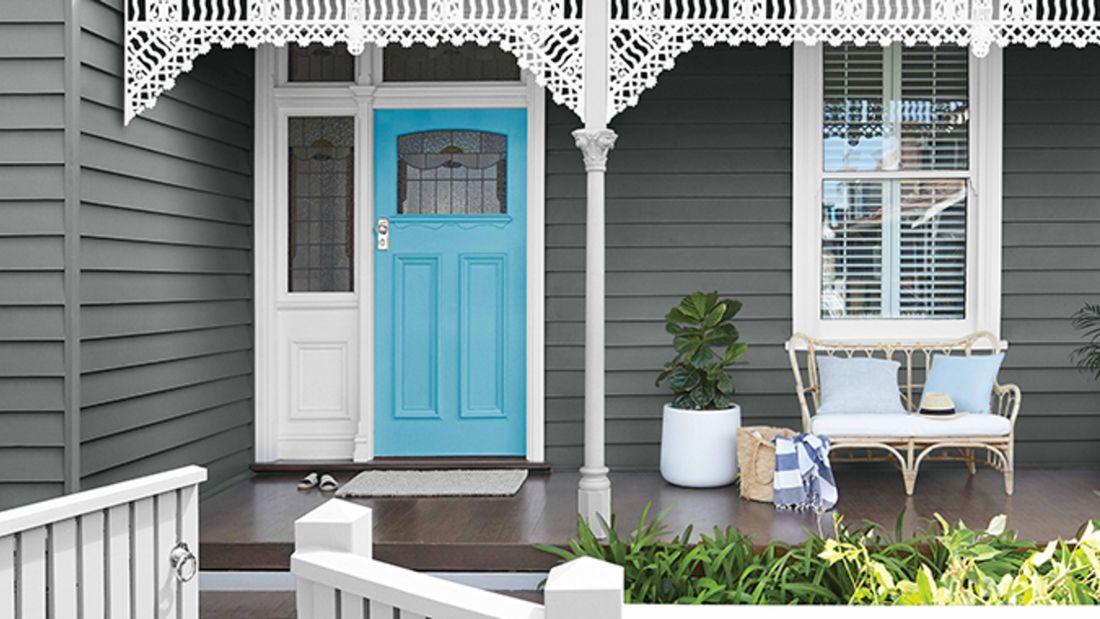 Sky blue front door in a modern grey weatherboard villa.