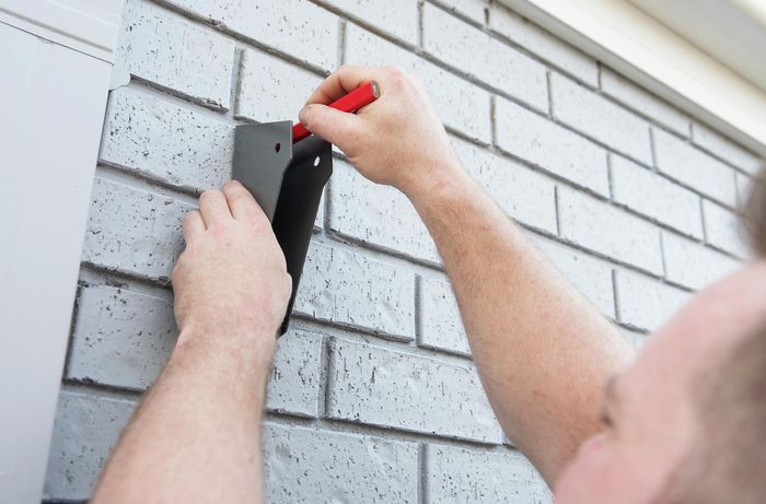 Person marking clothesline bracket position on wall