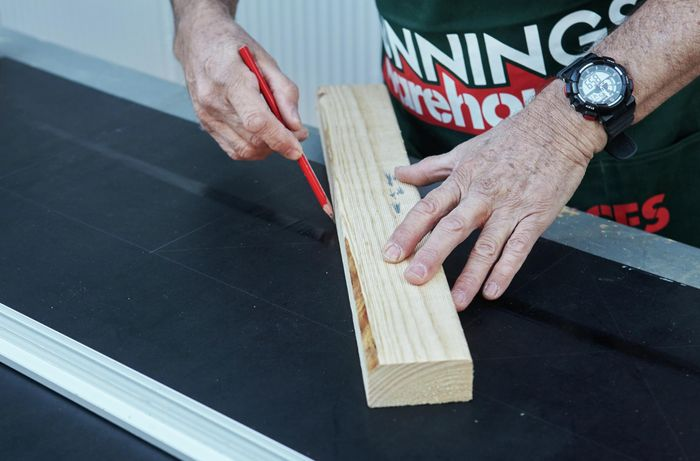 A scrap piece of timber being used as a ruler to plot out the centre of squares drawn out in a vertical garden tier for pot plants