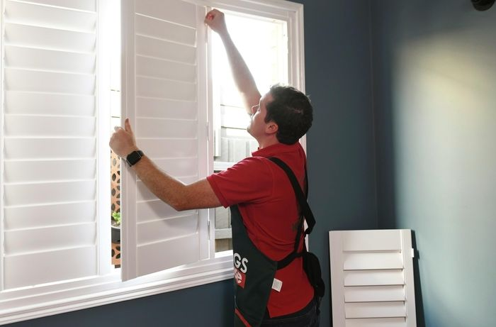 Person attaching shutter panels to the frame with hinge pins