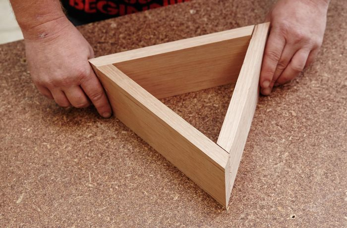 A person fitting three pieces of timber together to form a triangle