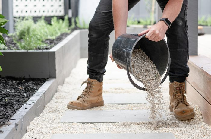 Person pouring gravel from a bucket around paving stones.