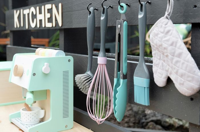 A close up of a completed outdoor play kitchen complete with plastic utensils and a play coffee machine