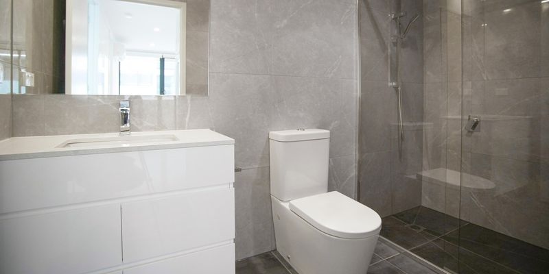 Grey Marble-walled bathroom with a sink, toilet and shower.