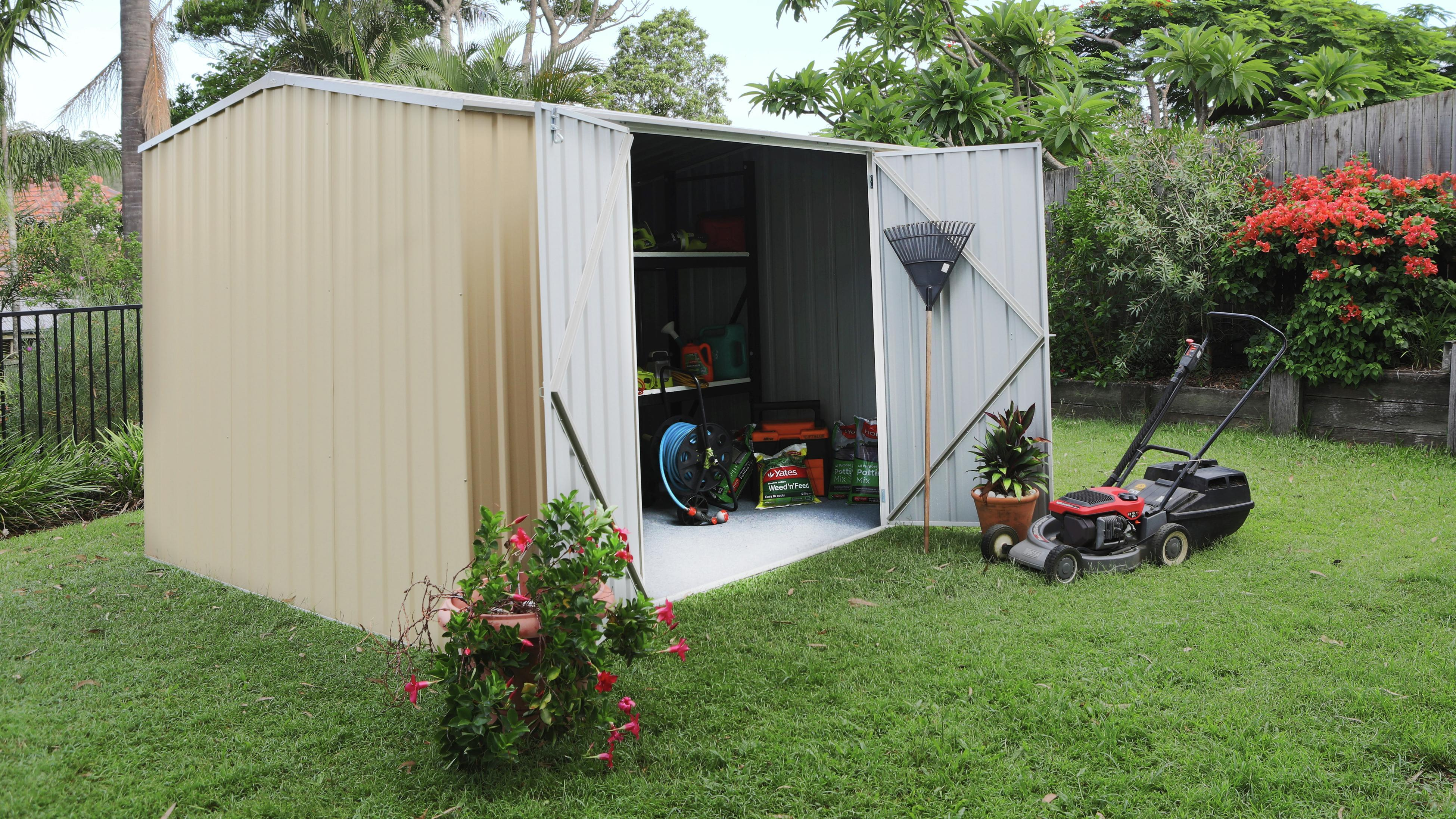 Cream shed in backyard surrounded by palms. Door open with lawn mower showing.