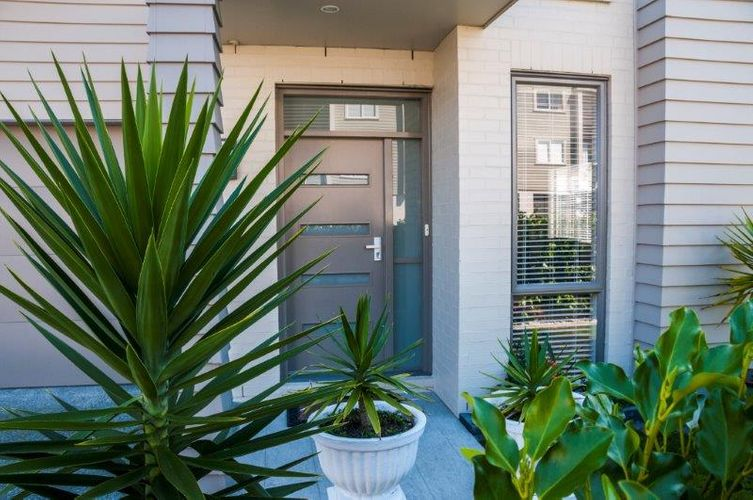 Front entryway to home with potted ferns and grey door