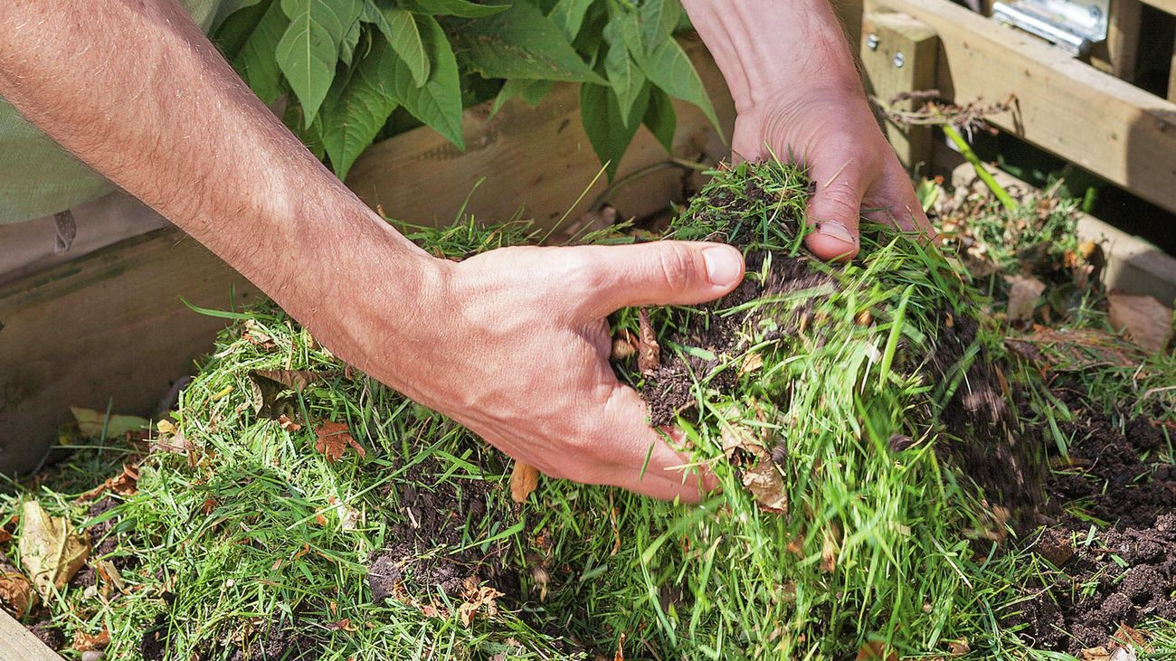 A person mixing grass cuttings into soil in a compost bin