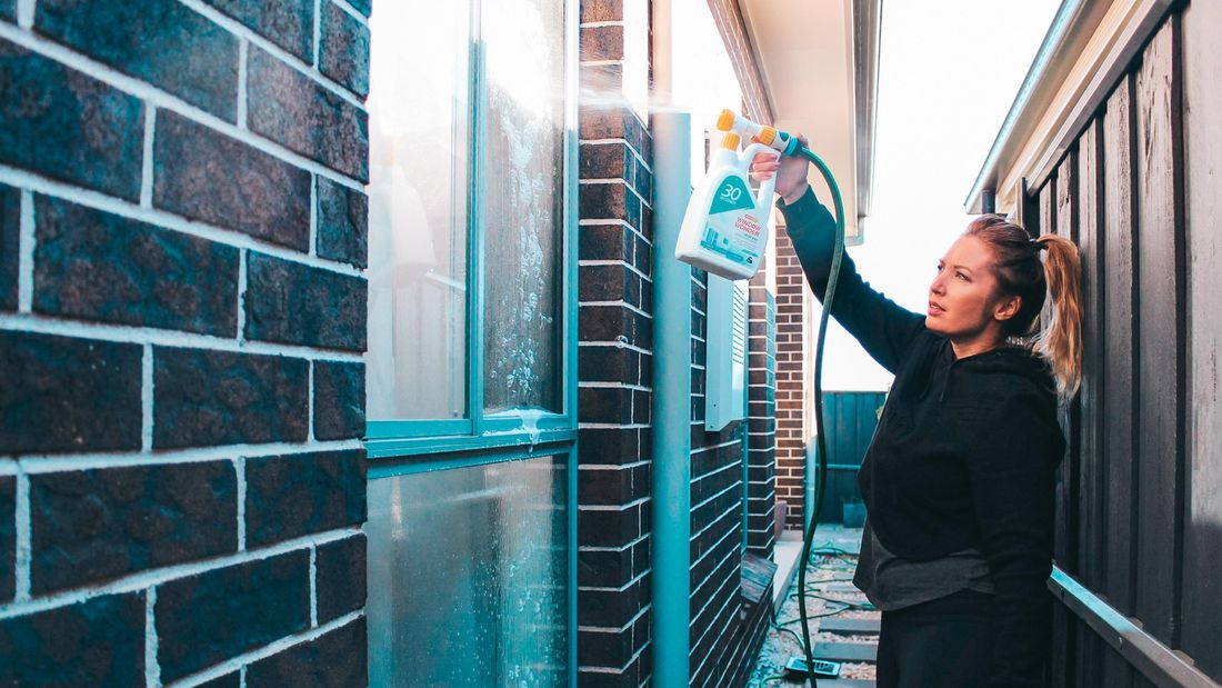 A woman holding the 30 seconds outdoor cleaner attached to a hose and spraying the liquid onto a window on the side of a house.