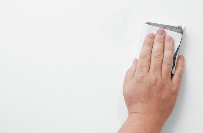 Sanding the patched hole in the wall