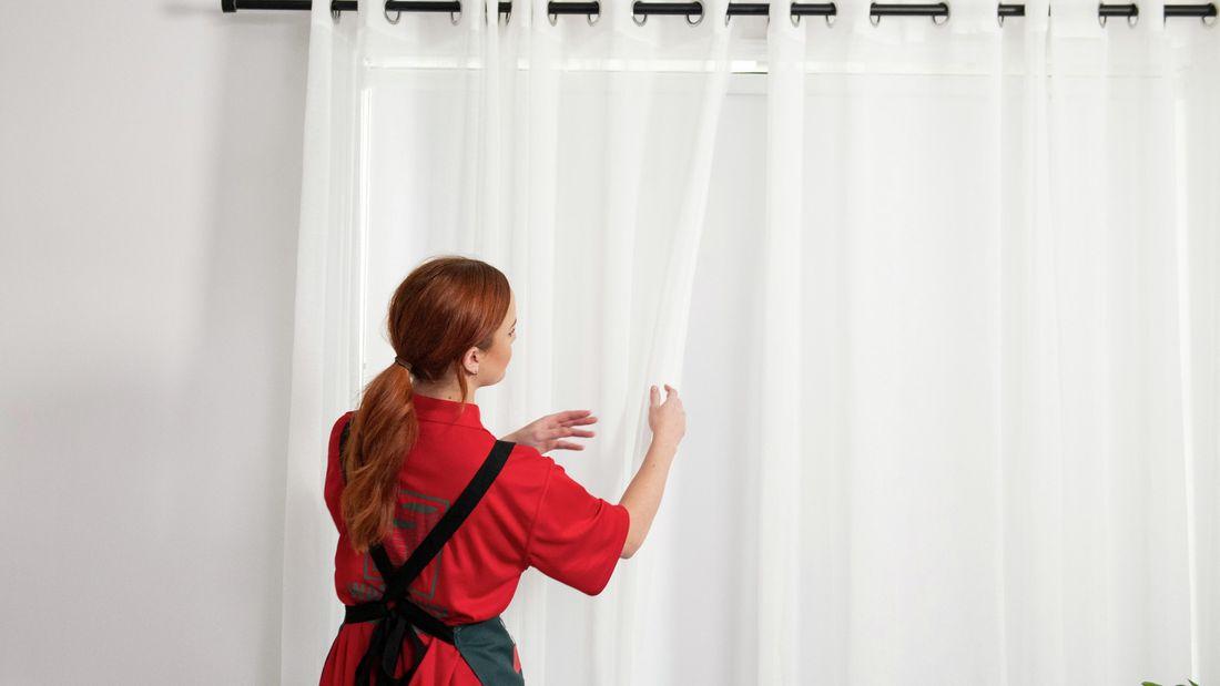 Bunnings Team Member opening curtains in a bedroom.