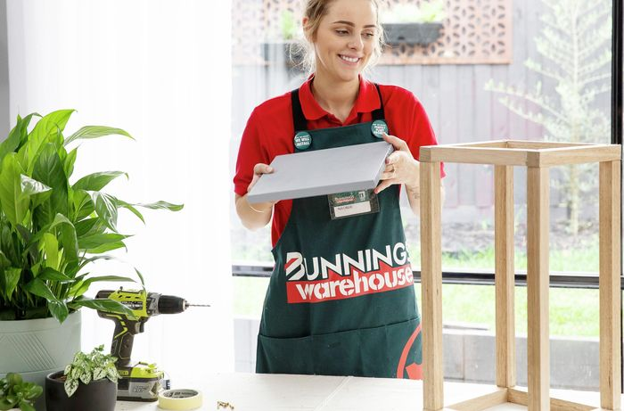 A Bunnings team member adding a solid base to a wooden plant stand