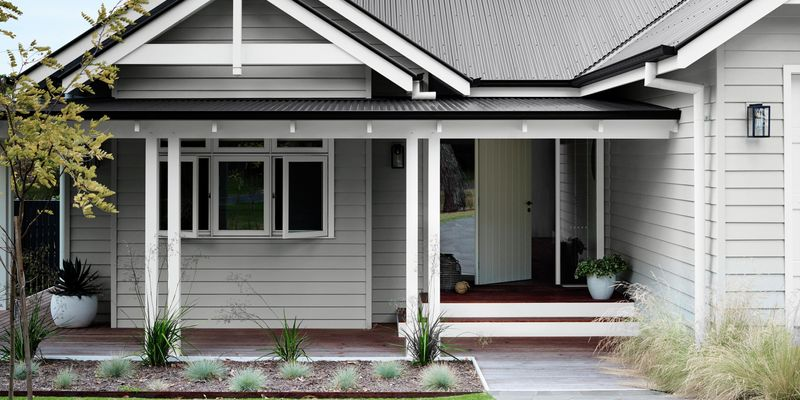 Grey house front and entryway in a front yard