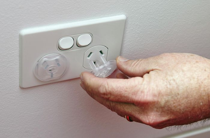 A person inserting a power point protector into a power point