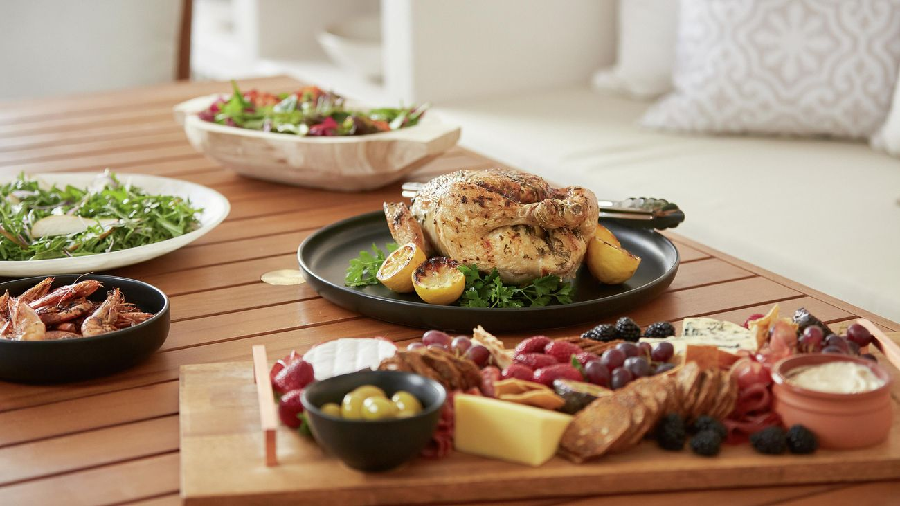 Barbecued chicken and prawns, salads and an antipasto platter on an outdoor dining table