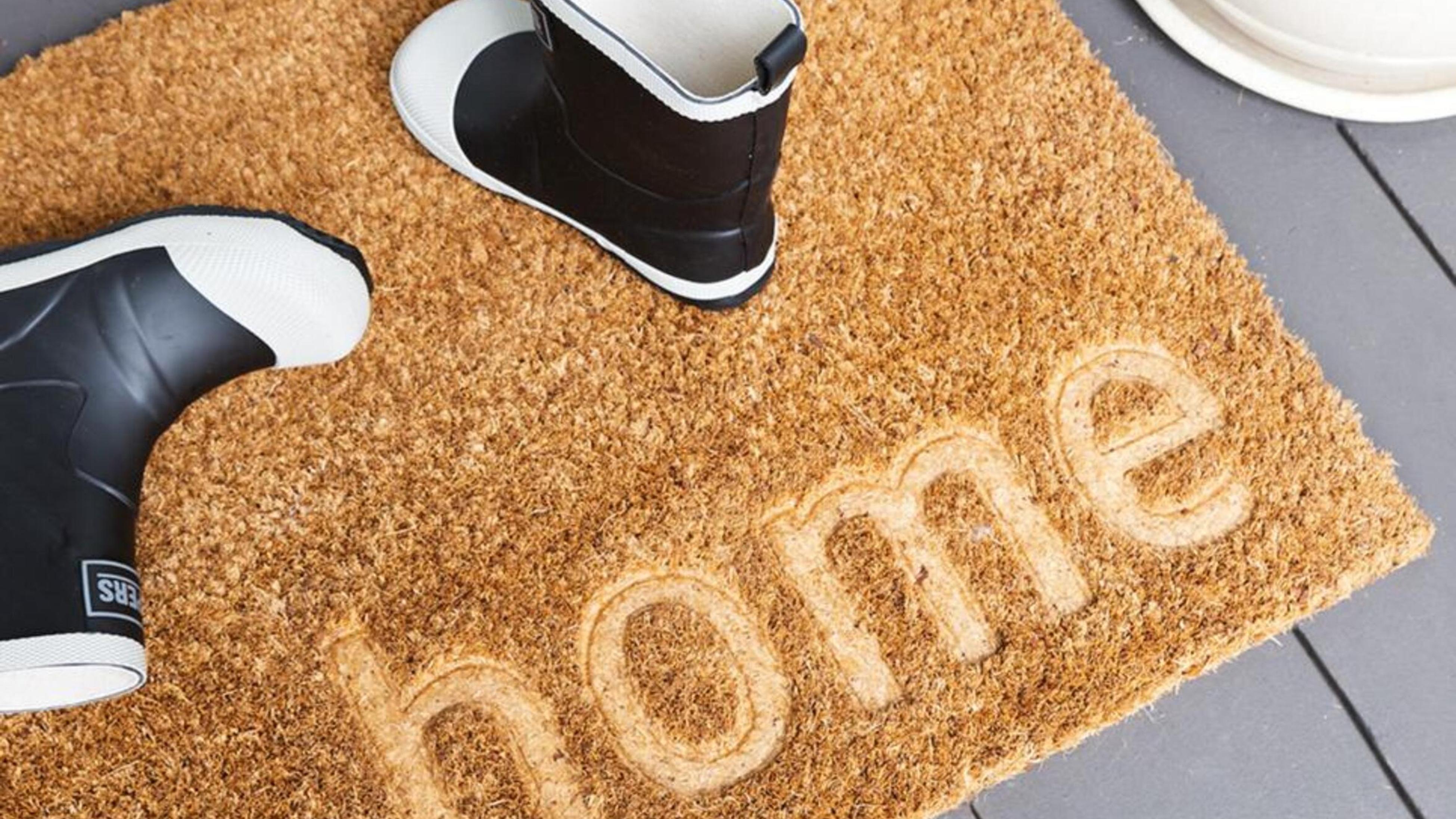 Door mat with gumboots on it.