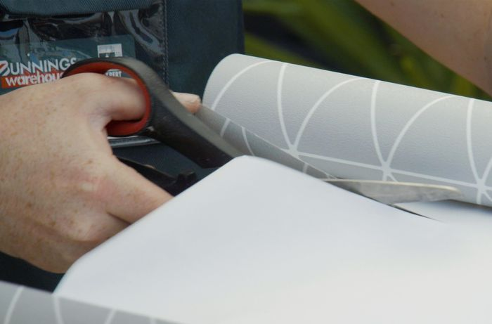 Person cutting a roll of wallpaper with scissors