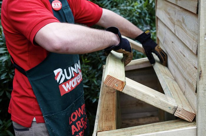A wooden access hatch being built into the side of a chicken coop by a Bunnings team member