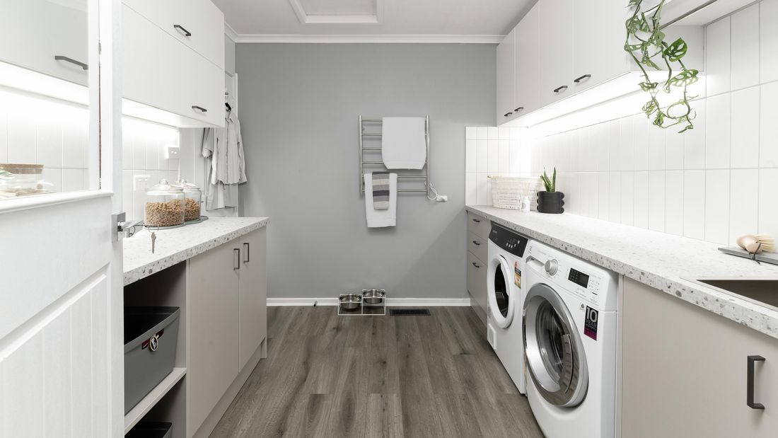 Laundry with cabinets, washer, dryer and timber flooring.