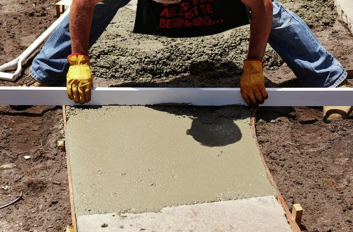 Bunnings team member using a straight edge to level the wet concrete surface