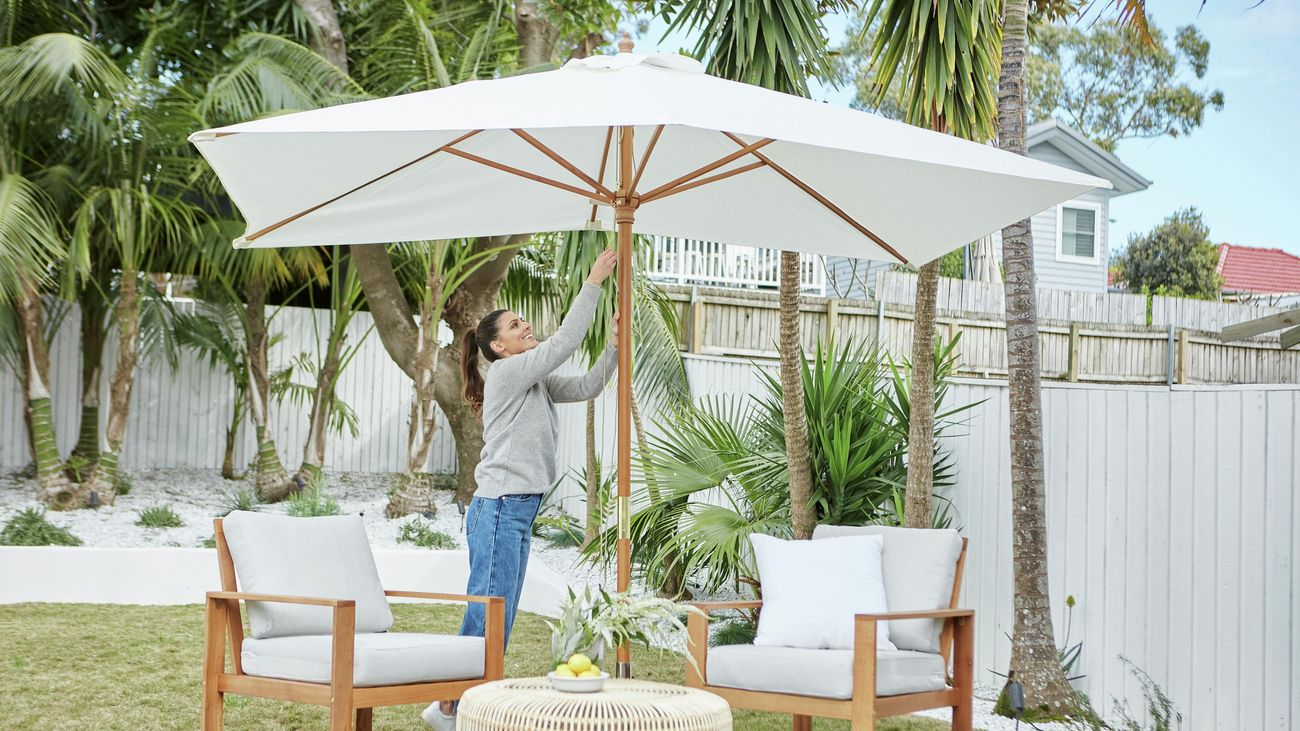 A white market umbrella covers two cushioned outdoor armchairs