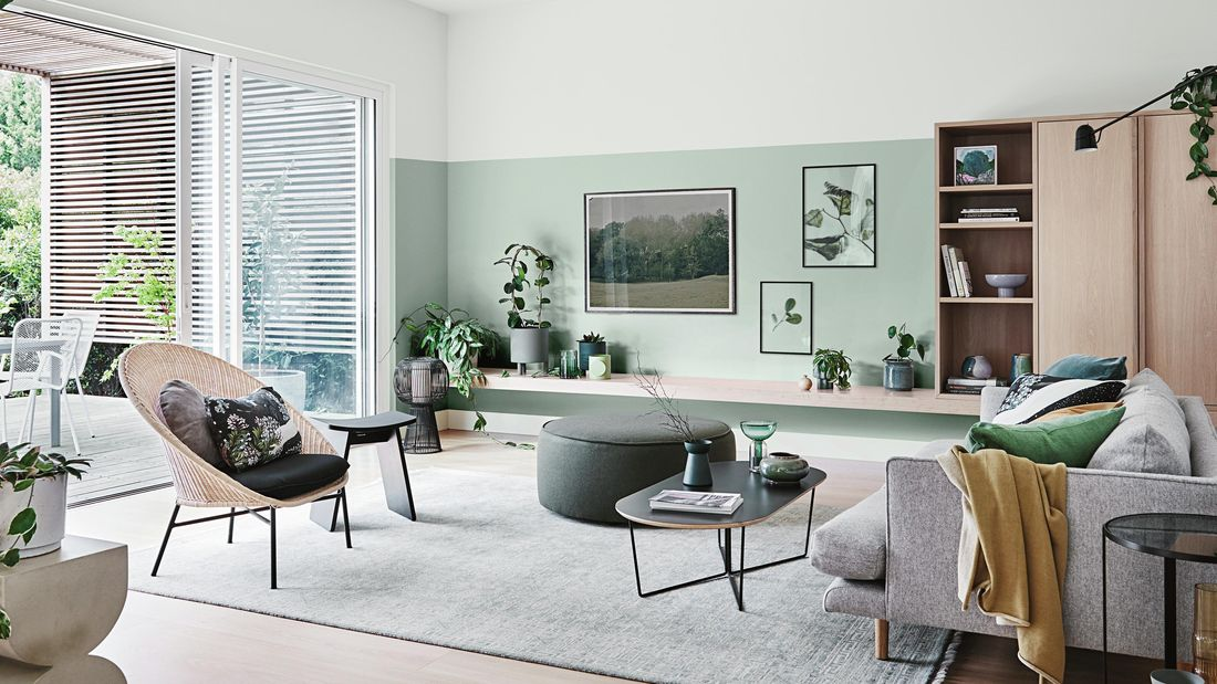 Living room with mint green painted wall, seating and indoor plants