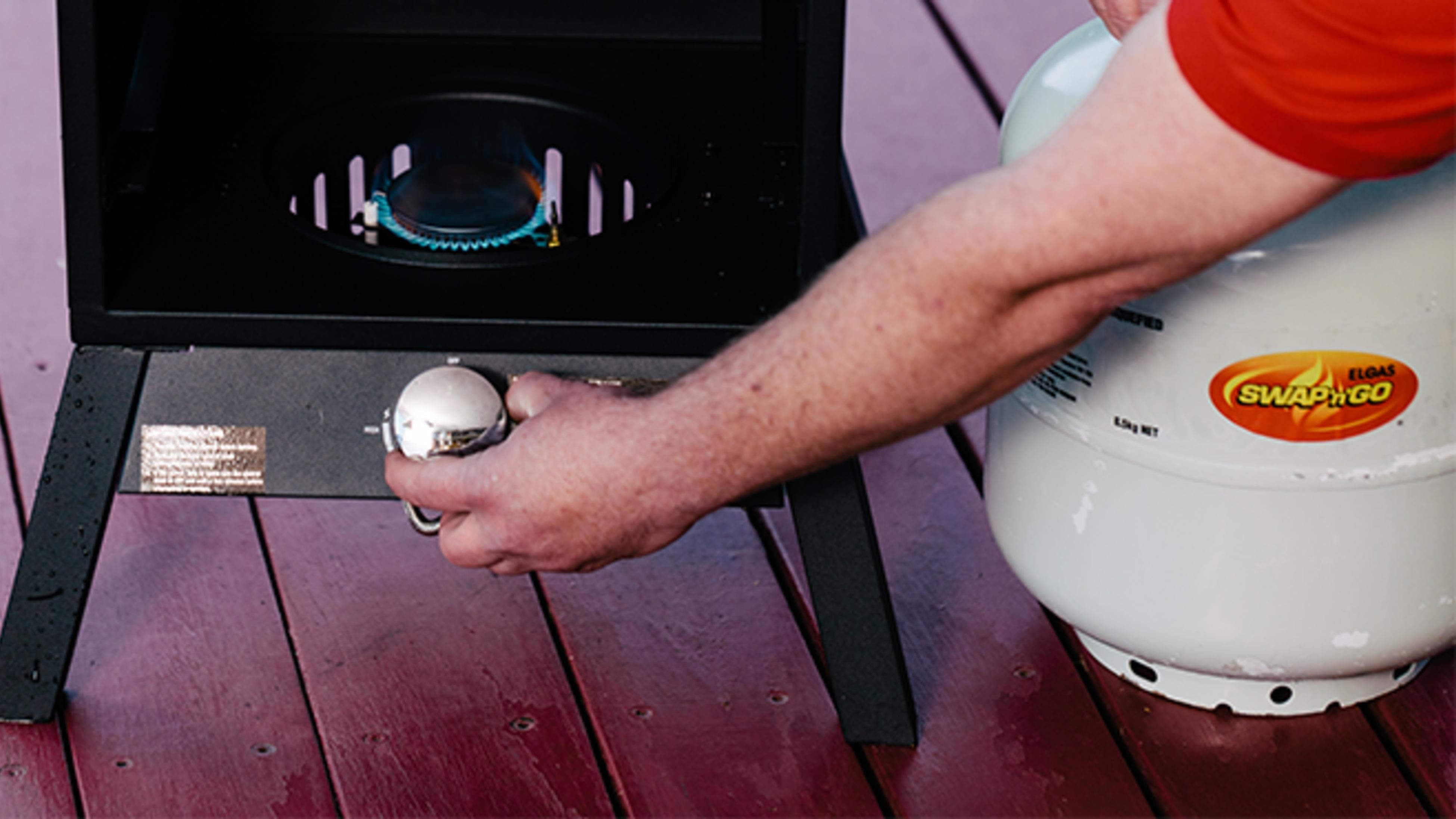 Person adjusting dial on BBQ.