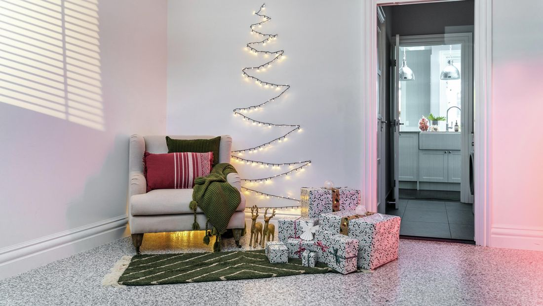 Christmas tree made of fairy lights on a lounge wall with an armchair positioned and an assortment of wrapped gifts in front of it