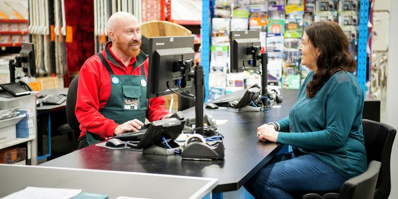 Bunnings team member assisting a customer in-store with a query using a computer
