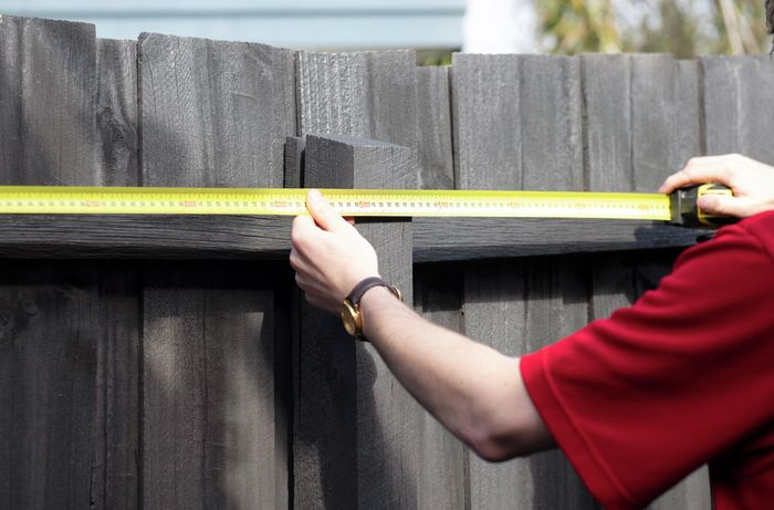 Bunnings team member measuring the topmost part of a fence