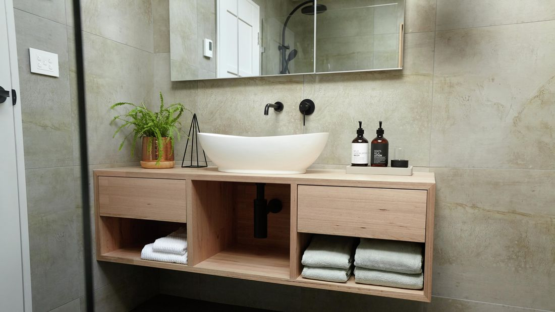 A floating timber vanity with a curved white basin on top and towels below the drawers