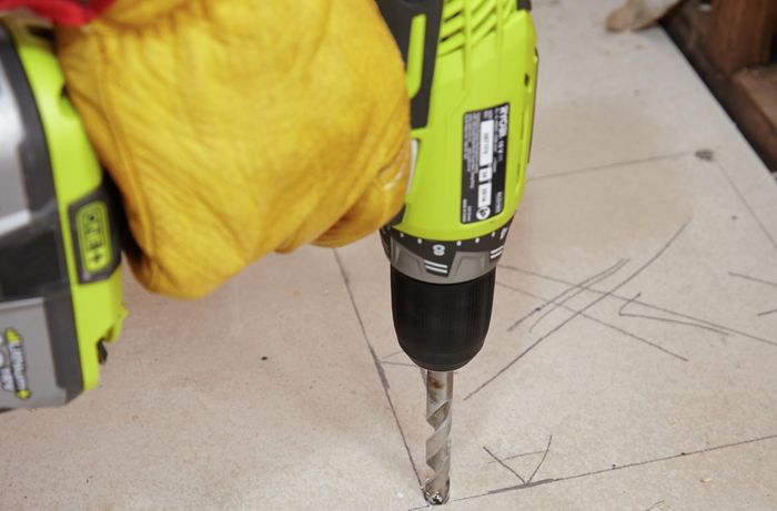A hole being drilled into the floor sheet to make room for a shower sump