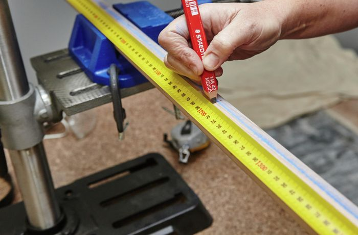 Person using measuring tape and pencil to mark up sides of wooden ladder.