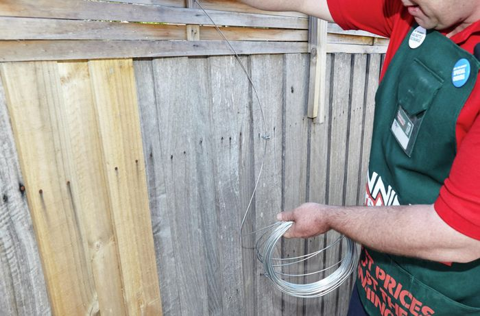 A person threading wire through a hook eye in a paling fence