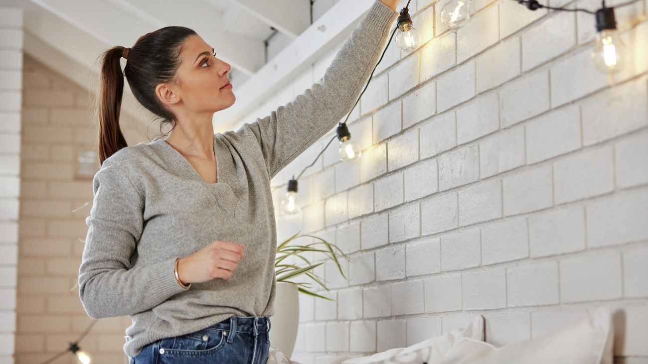 A woman hanging festoon party lights in an outdoor alfresco area