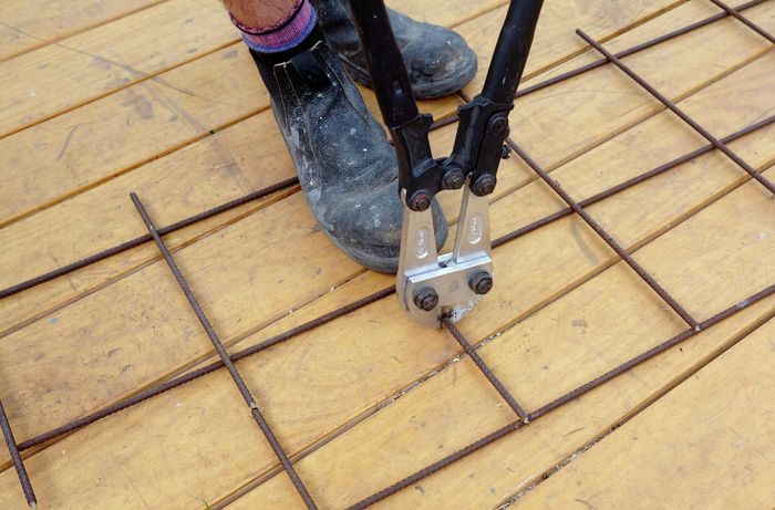 Boltcutters being used to trim a wire mesh length to size