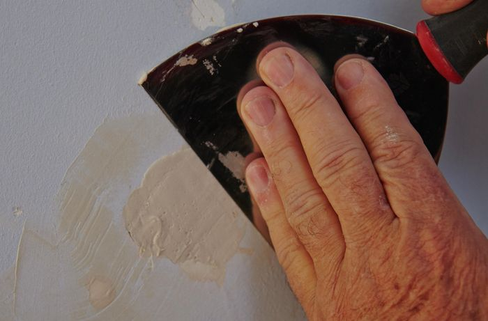 A paint scraper being used to scrape away excess plaster from a repaired hole