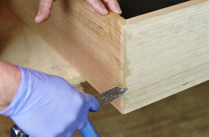 Applying putty to fill any gaps or holes in the dog bed