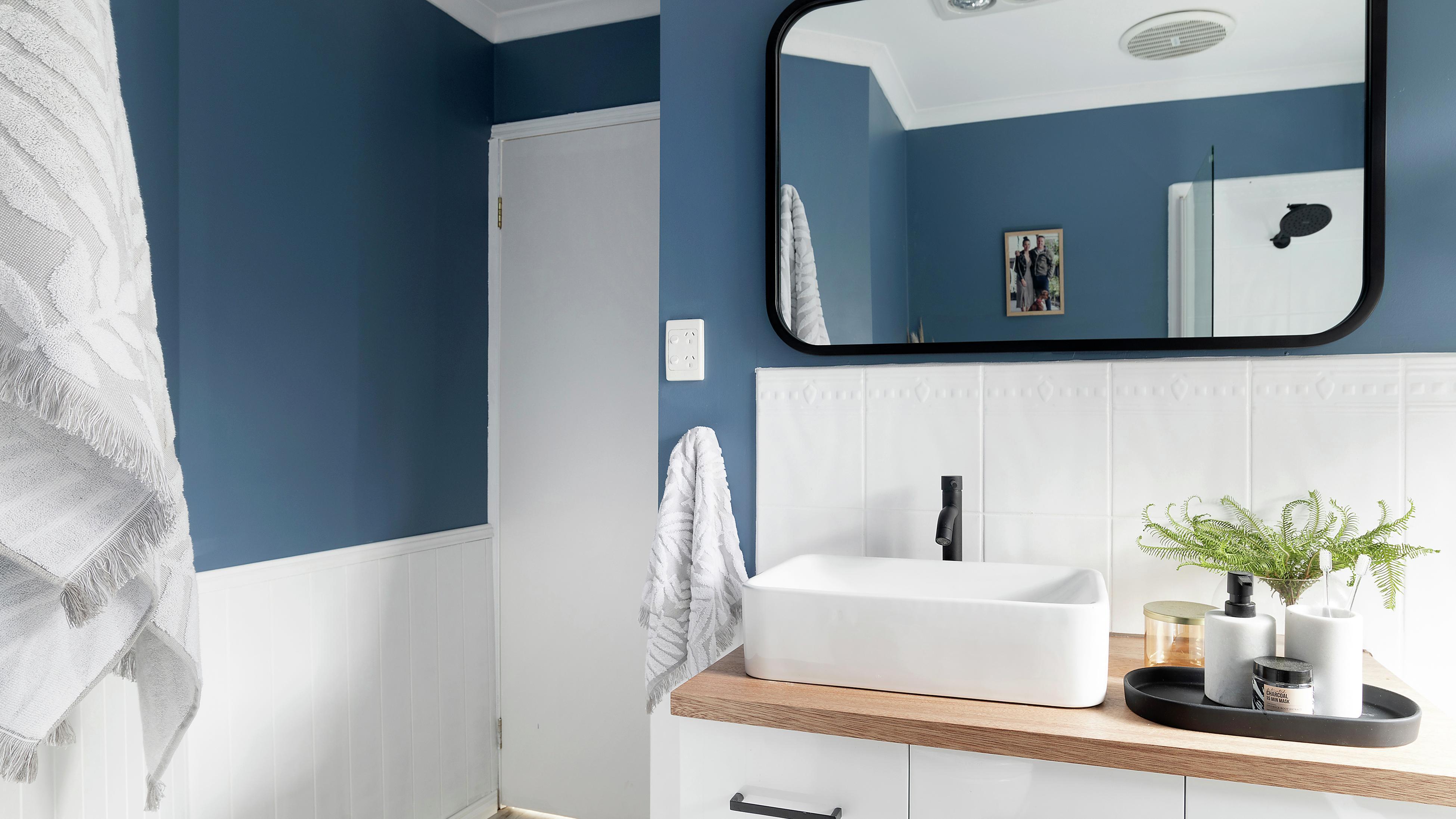 Bathroom with blue walls featuring vanity, mirror, towels.