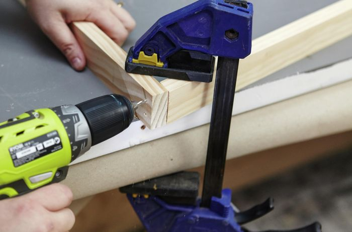 Person drilling two bits of timber together to create bookshelf side.