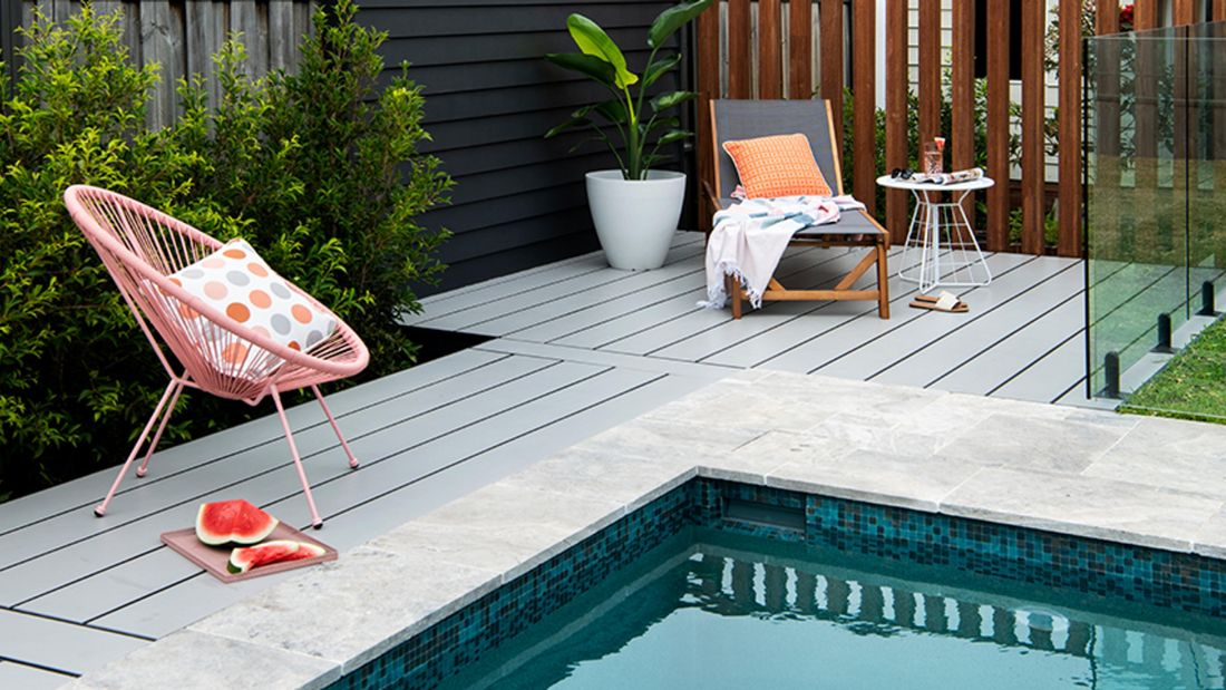 Pool with pale coloured decking and outdoor furniture