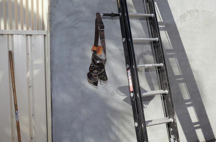 A tool belt hanging off a ladder limb on an extension ladder