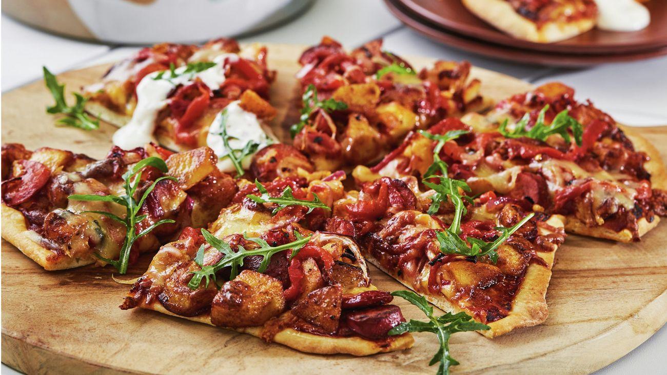Chorizo and potato pizza on a round timber board