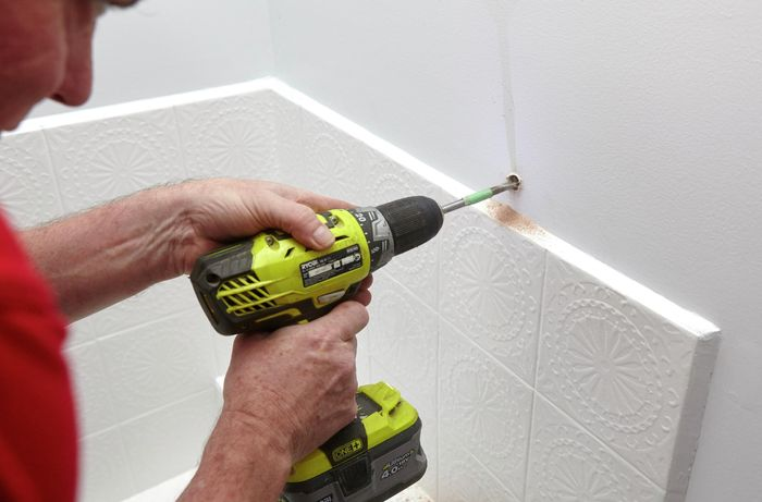 Person drilling a on screw into white bathroom wall.