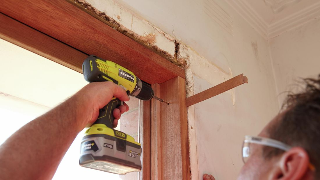 Drilling pilot holes at the top of the window frame