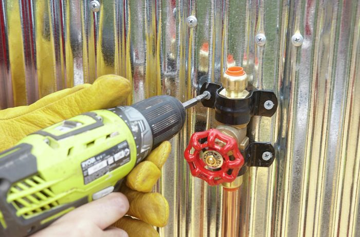 Person drilling brace into metal wall to hold tap in place.