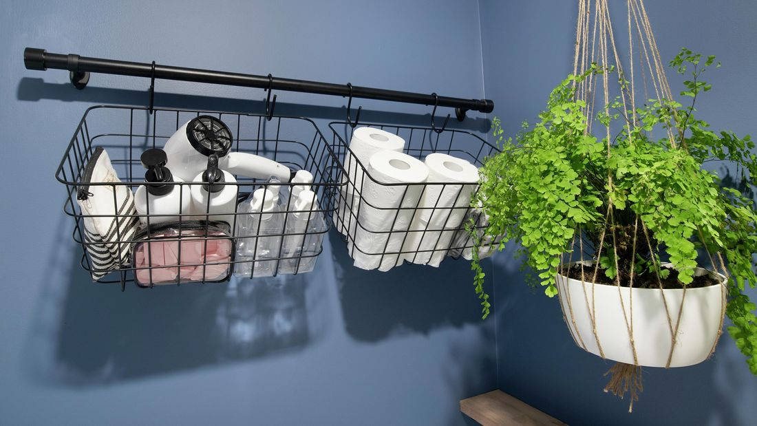 A wall mounted rail holding storage baskets in a bathroom